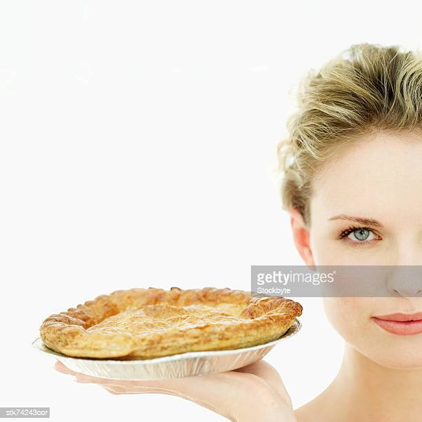close-up of woman holding up a pie