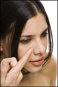 Closeup of woman inserting contact lens