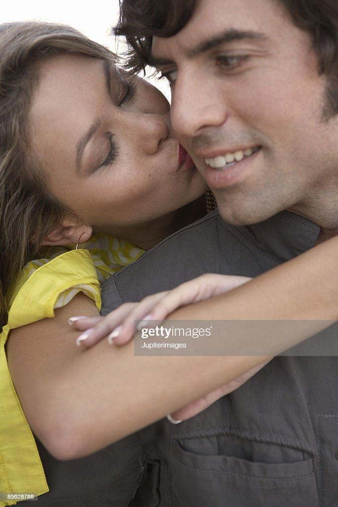 Close-up of woman kissing man on cheek : Stock Photo