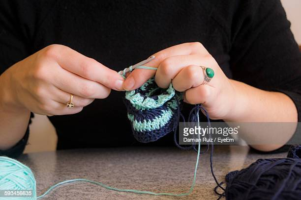 Close-Up Of Woman Knitting On Table