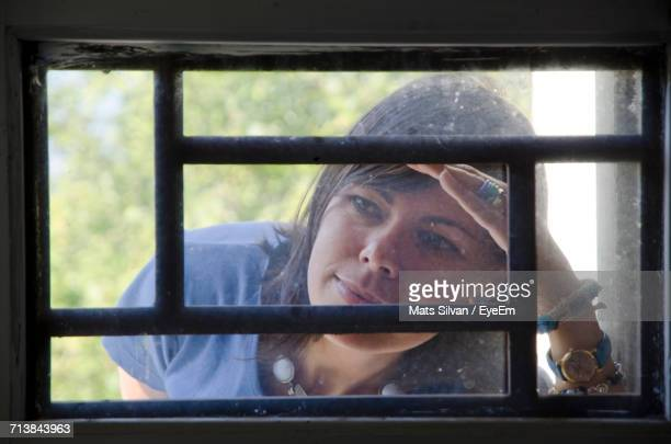 Close-Up Of Woman Peeking Through Window