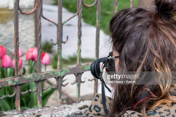 Close-Up Of Woman Photographing Flowers By Railing Using Camera