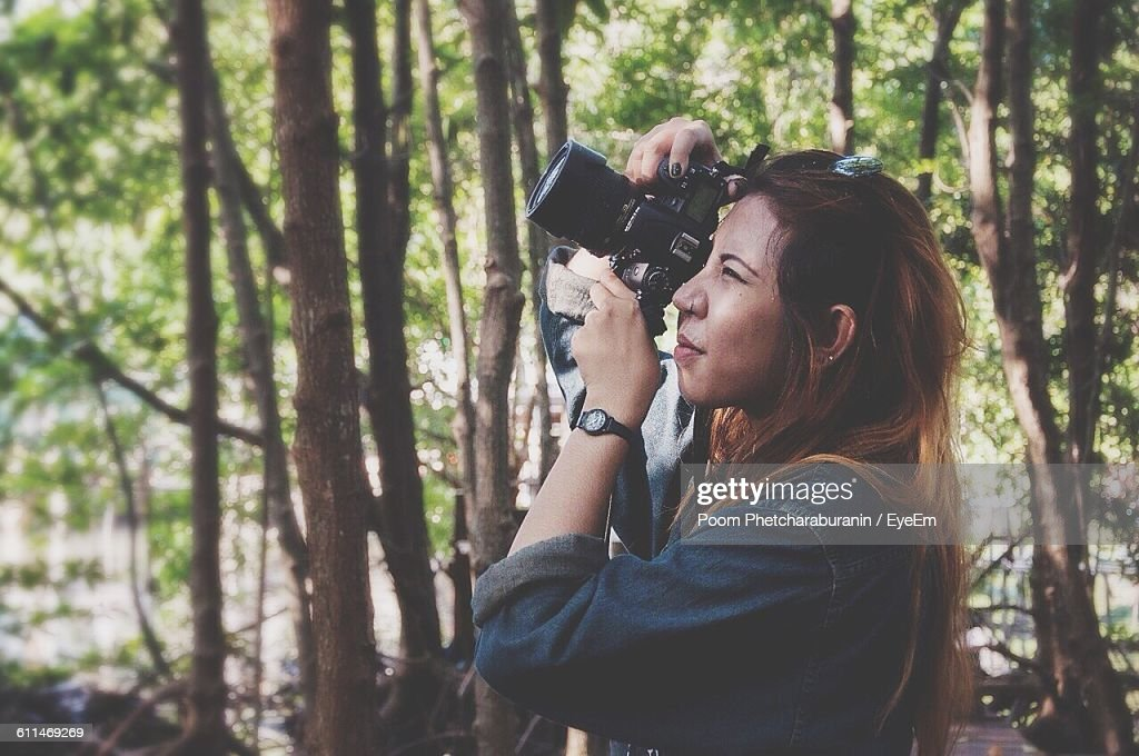 Close-Up Of Woman Photographing With Camera Against Trees : Stock Photo