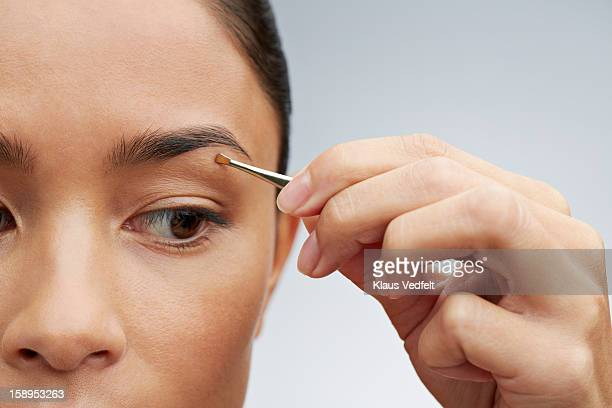 Close-up of woman plucking her eyebrows