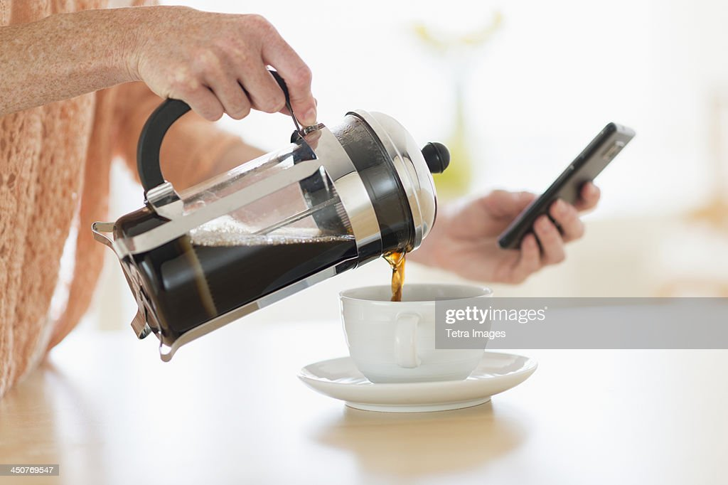 Close-up of woman pouring coffee and looking at phone