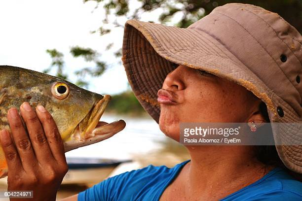 Close-Up Of Woman Puckering Lips While Holding Fish