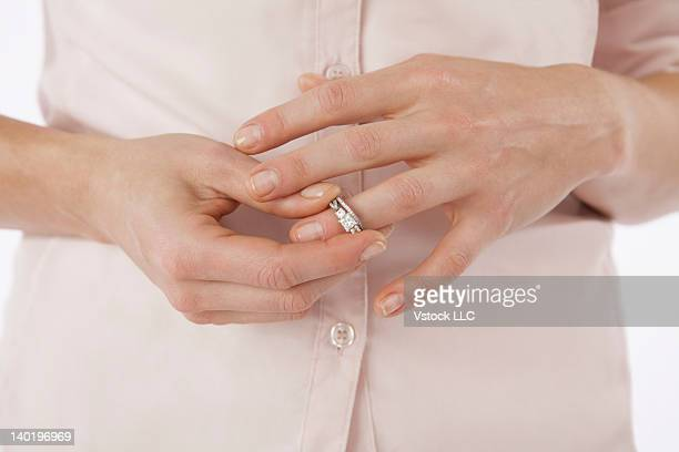 Close-up of woman removing wedding ring from finger