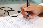 Closeup of woman signing document. Contract and glasses lying on table. Deal concept. Cropped view.