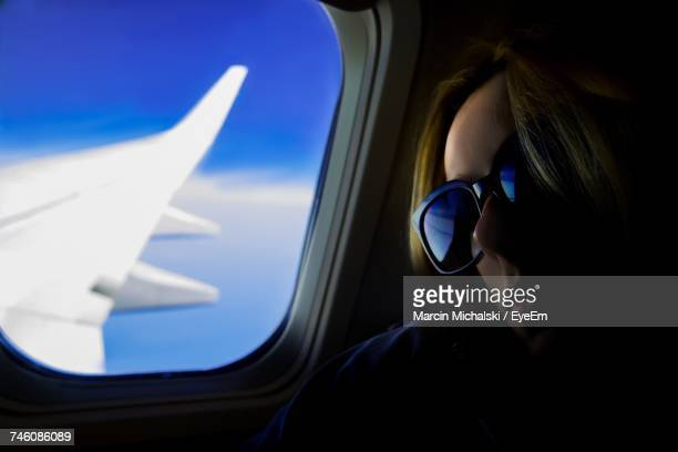 Close-Up Of Woman Sitting By Airplane Window