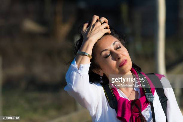 Close-Up Of Woman Standing With Hand In Hair On Sunny Day