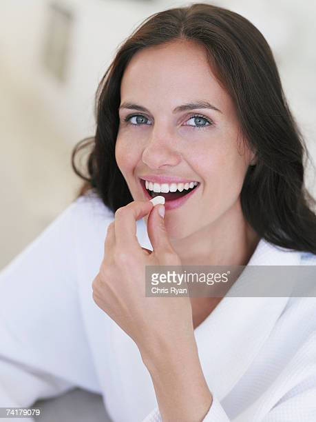 Close-up of woman taking pill