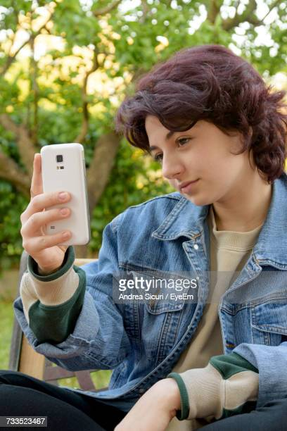 Close-Up Of Woman Taking Selfie While Sitting On Bench At Park