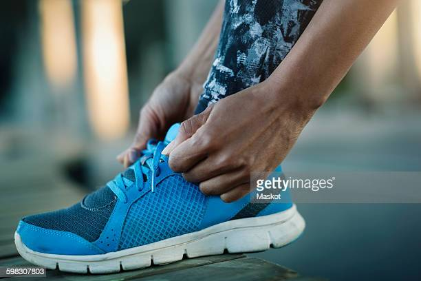 Close-up of woman tying shoelace on bench