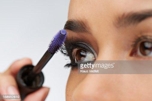 Close-up of woman using eyelash brush