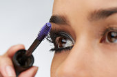 Close-up of woman using eyelash brush