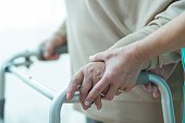 Close-up of woman using walker assisted by carer