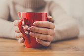 Woman holding cup of tea while sitting at wooden table in cozy coffee shop, shallow depth of field. Girl enjoying mug with hot drink at urban cafe and warming hands