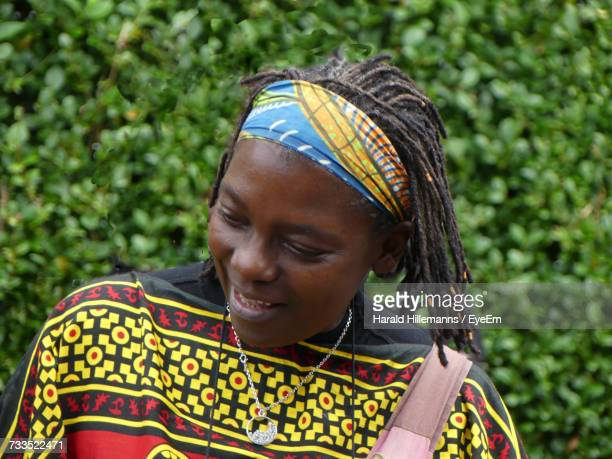 Close-Up Of Woman With Dreadlocks Wearing Colorful Bandana Against Plants
