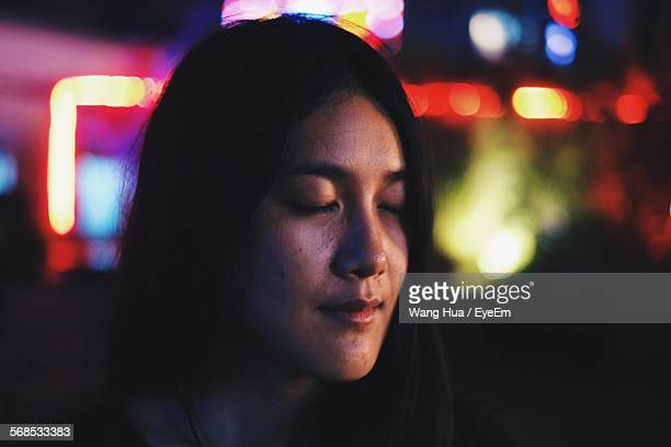 Close-Up Of Woman With Eyes Closed In Illuminated City At Night