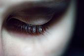 A close-up shot of a woman with long eyelashes that is looking down in sadness.