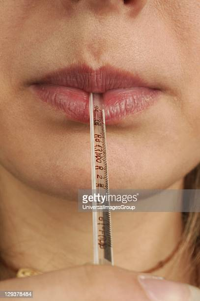 Closeup of woman with mercury thermometer in her mouth She is taking her own temperature to selfdiagnose fever symptoms of flu She is using an oral...