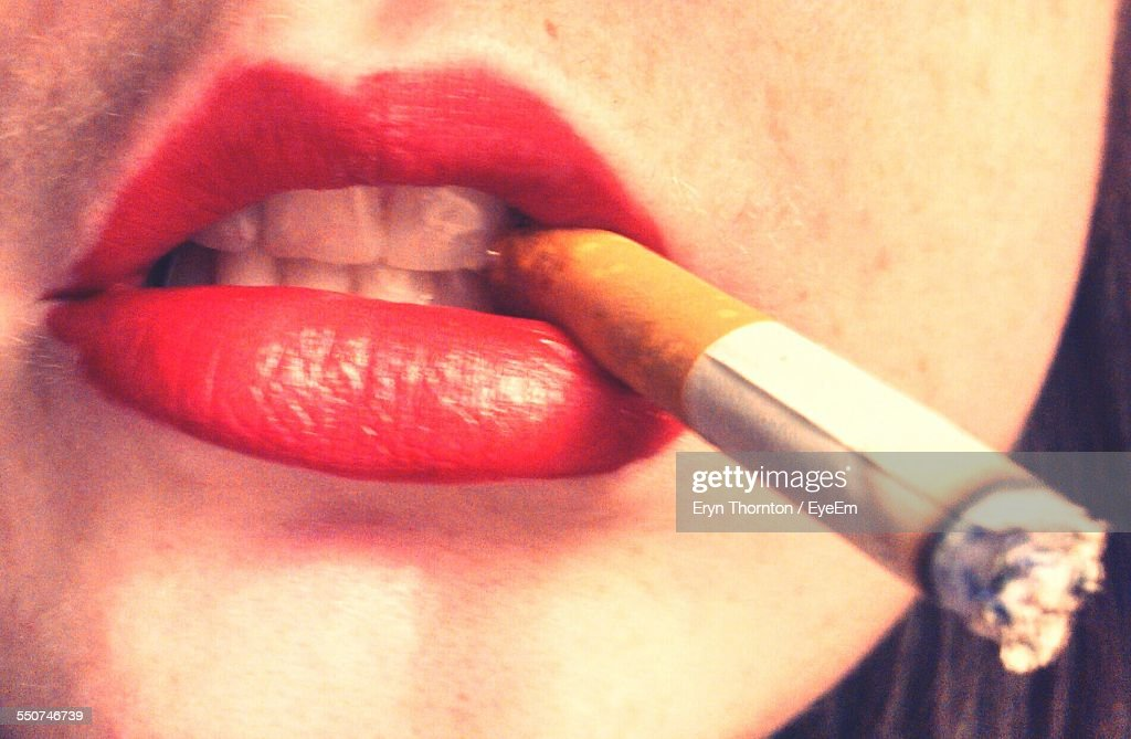 Close-Up Of Woman With Red Lipstick Holding Cigarette In Mouth