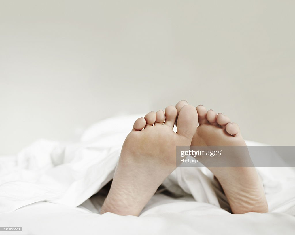 Close-up of woman's feet in bed : Stock Photo