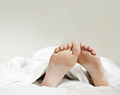 Close-up of woman's feet in bed