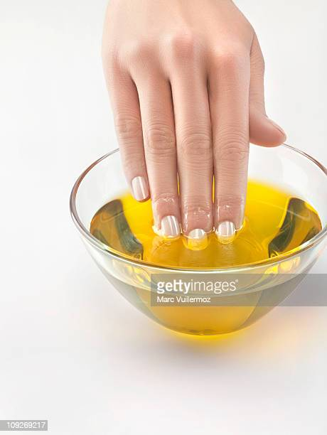 Close-up of woman's hand in bowl of olive oil