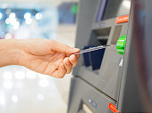 Close-up of woman's hand inserting debit card into an ATM machine. Horizontal shot.