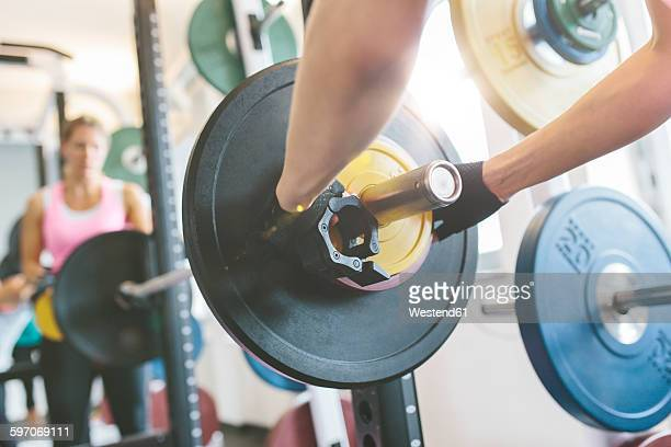 Close-up of womans hand putting weights on a barbell in gym