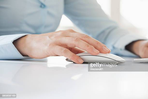 Close-up of womans hand using computer mouse