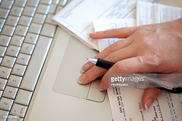 Close-up of woman's hand using trackpad to pay bills online