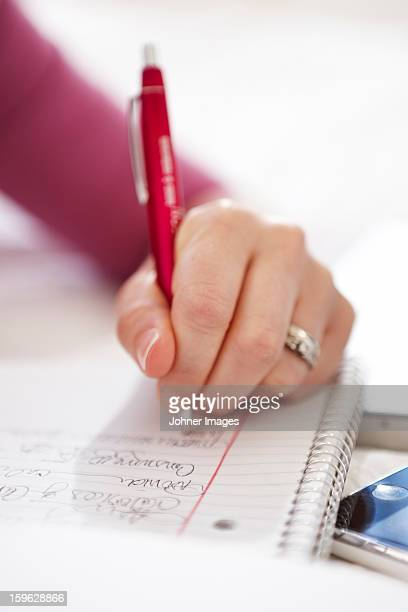 Close-up of womans hand writing on notebook