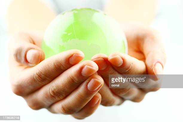 Close-up of woman's hands holding a bright green globe