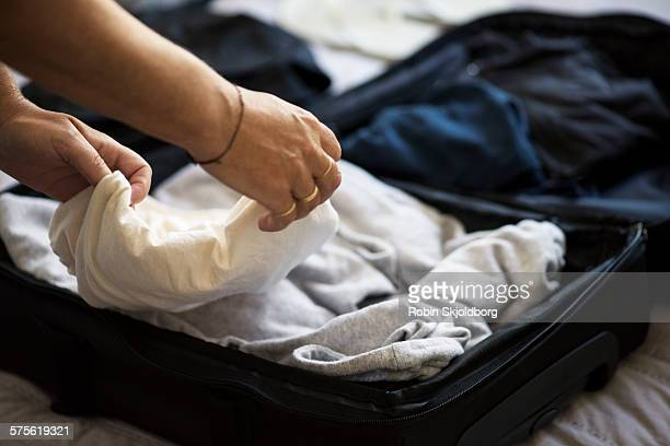 Closeup of Womans hands packing suitcase