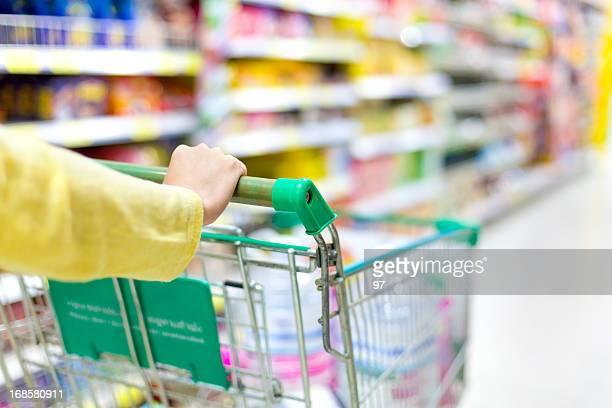 のクローズアップの女性の手を押すショッピングカート