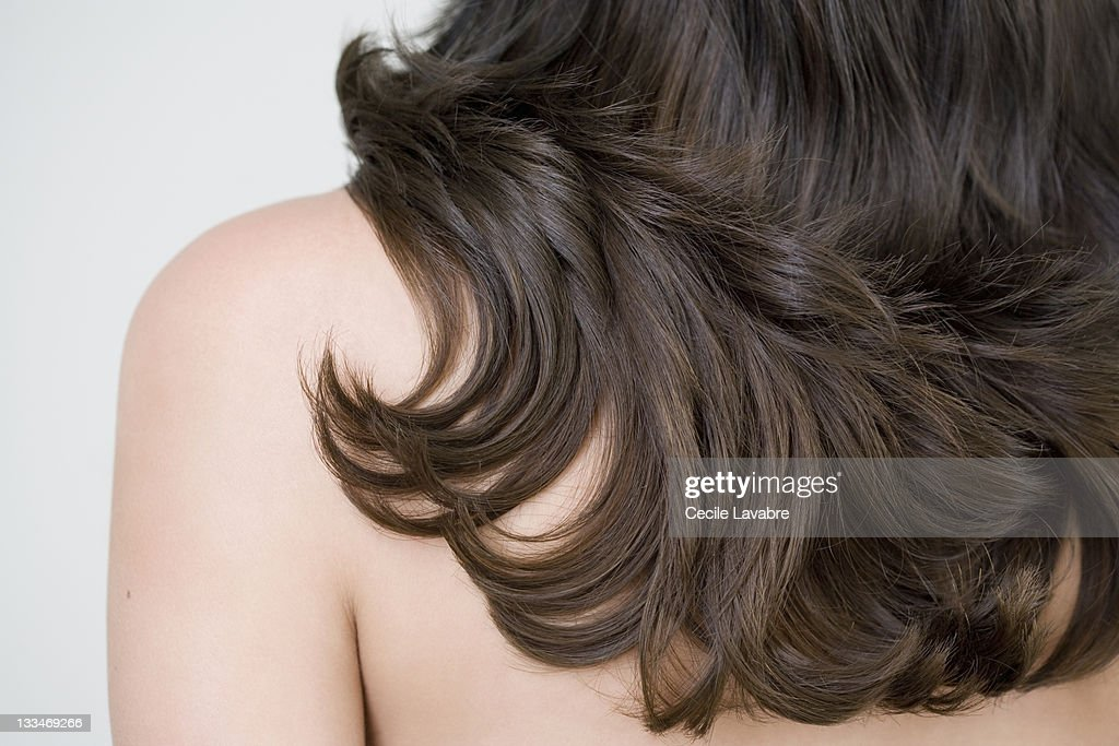 Close-up of woman's long brown hair over shoulder : Stock Photo