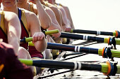 Close up women's rowing team - background and water blown out to emphasize rowers