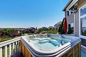 Close-up of wooden hot tub. Luxury house exterior. Blue sky background. Northwest, USA