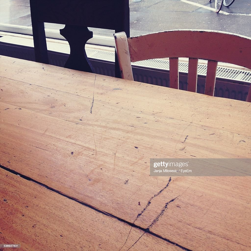 Close-Up Of Wooden Table By Chairs