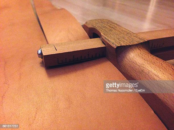 Close-Up Of Wooden Work Tool Cutting Leather For Making Belt In Workshop
