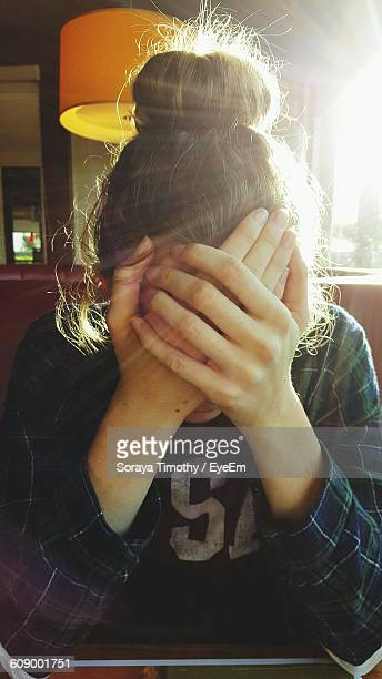 Close-Up Of Worried Woman Covering Her Face In Cafe