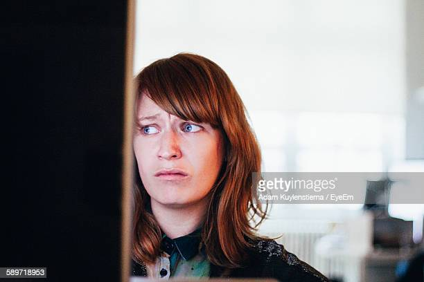 Close-Up Of Worried Woman While Sitting At Computer Desk In Office