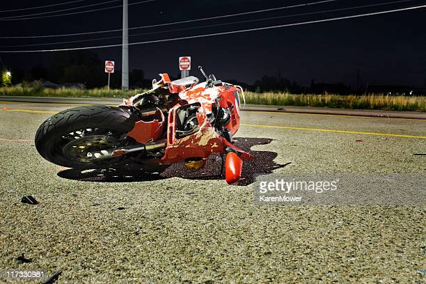 Close-up of wrecked red motorcycle on side of road