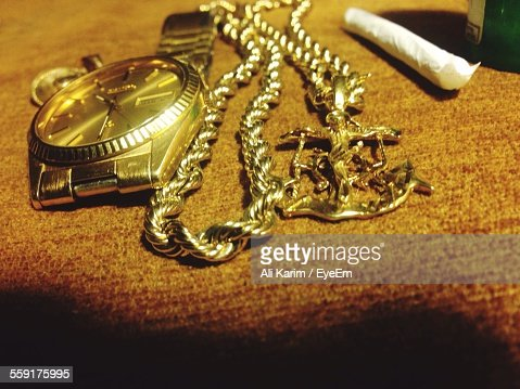 Close-Up Of Wristwatch And Gold Chain With Cross Shaped Pendant
