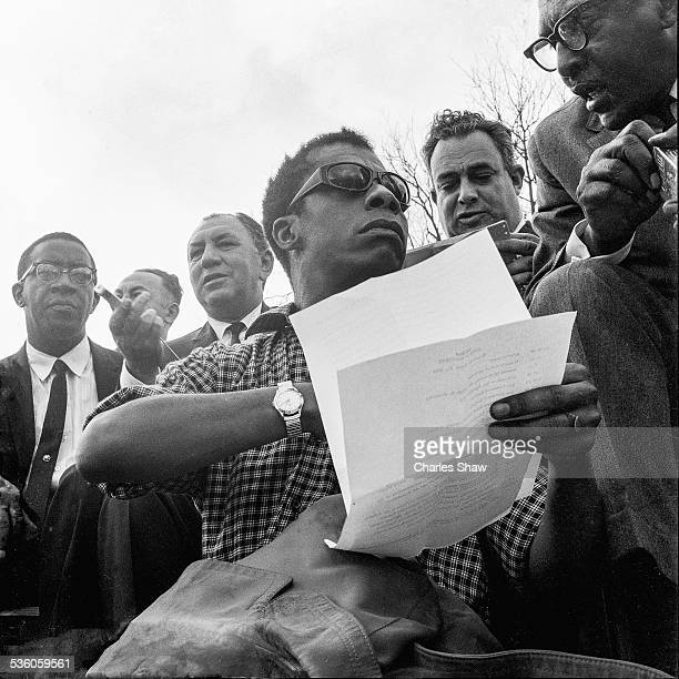 Closeup of writer and Civil Rights activist James Baldwin talks with an unidentified man on the podium in front of the Alabama State Capitol at the...