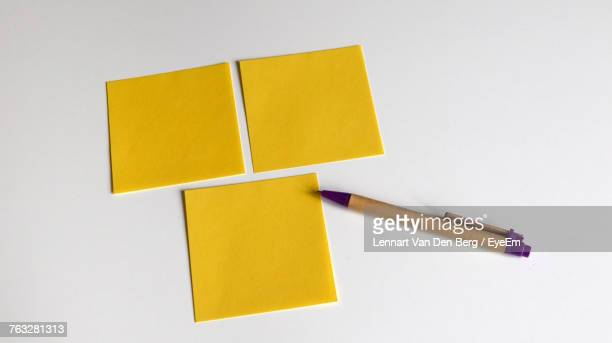 Close-Up Of Yellow Adhesive Notes And Pen Over White Background