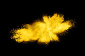 Abstract brown powder explosion. Closeup of yellow dust particle splash isolated on black background