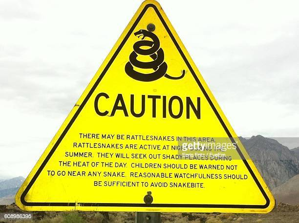 Close-Up Of Yellow Rattlesnake Warning Sign Against Sky